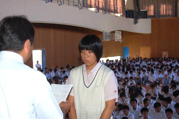 記念品を手渡す時任保彦校長と普通コース2年の浜田志保さん(喜入中)